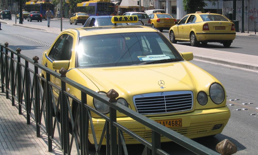 Ein gelbes Taxi hält in der griechische Stadt Athen am Straßenrand.
